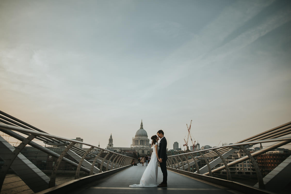 wedding couple posing on millenium bridge in london