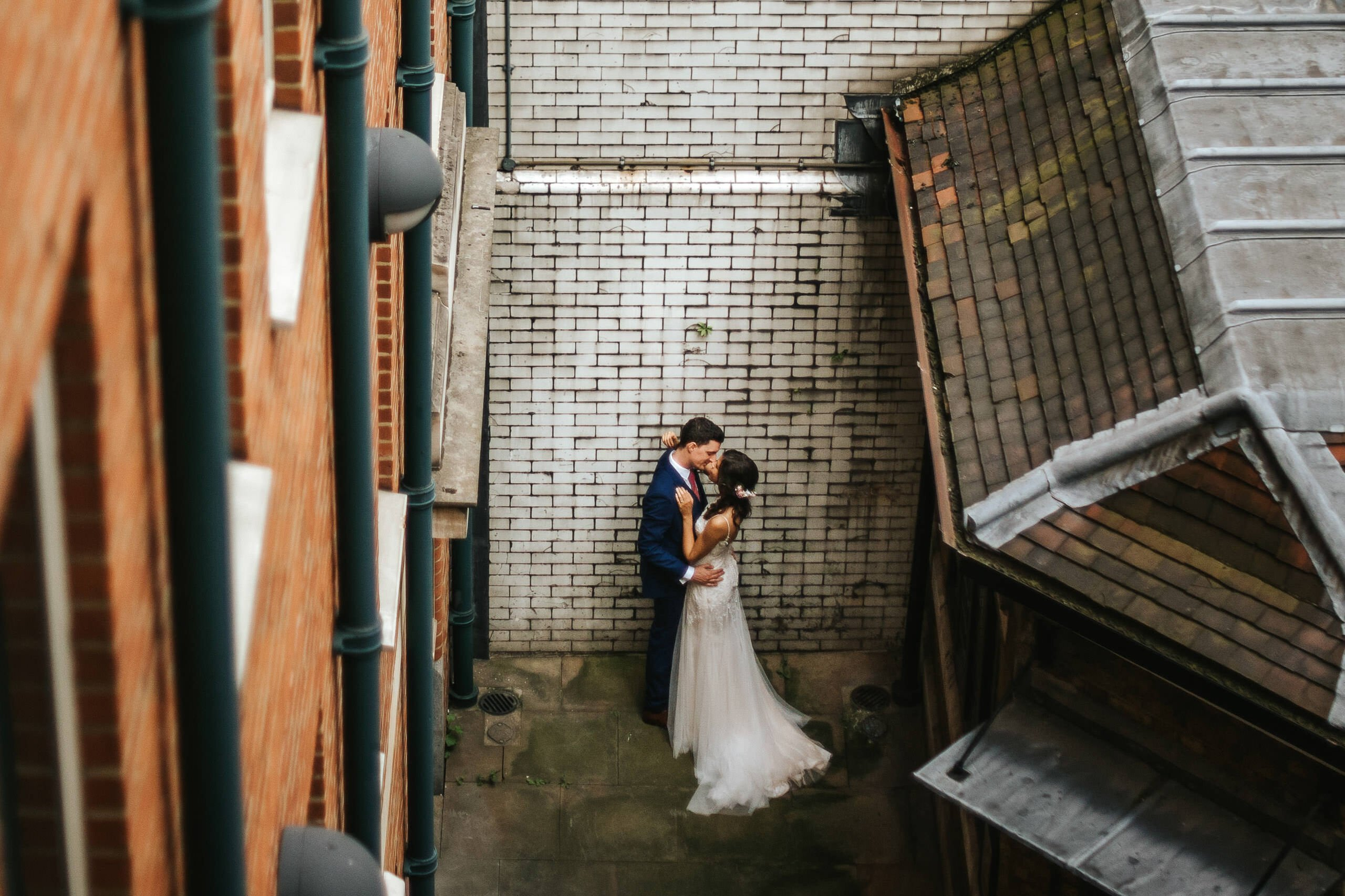 nelyweds kissing in the corner of the street by london wedding photographer
