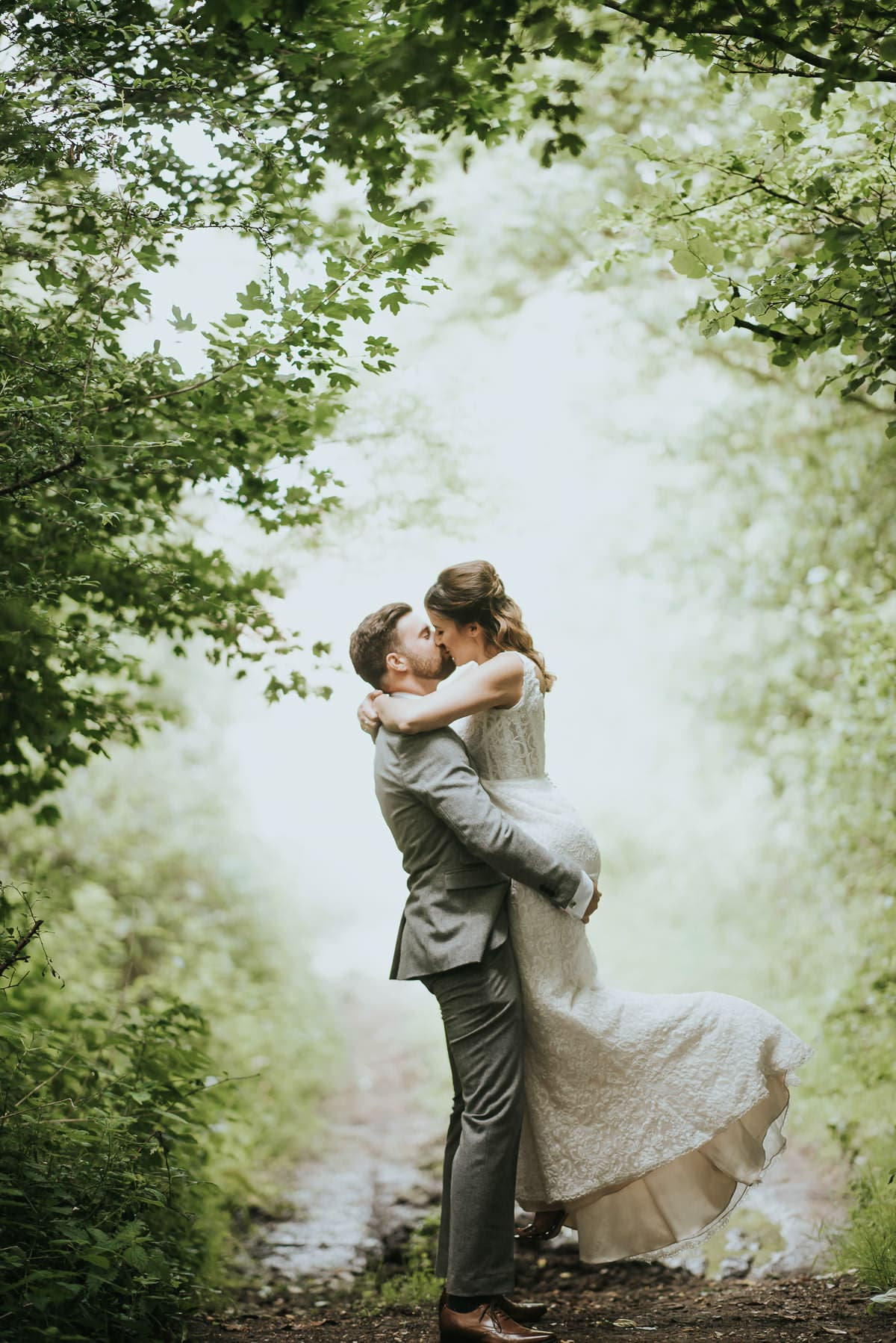 newlyweds on a forrest path in a magical light