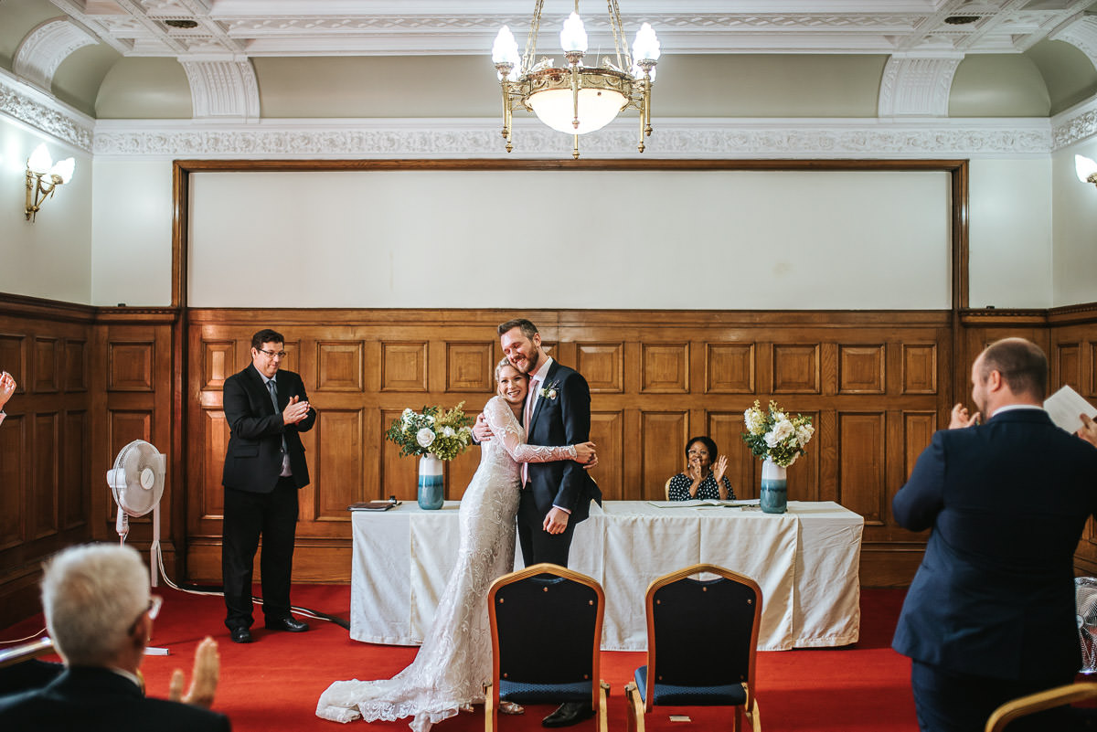 islington town hall wedding ceremony bride and groom hugging
