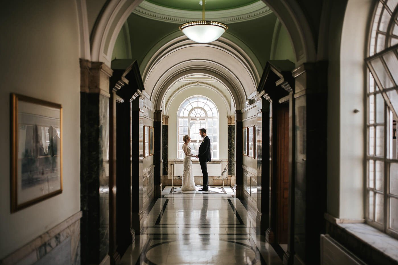 islington town hall wedding couple holding hands in the corridor